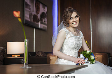 Bride with wedding flowers sitting on the chair