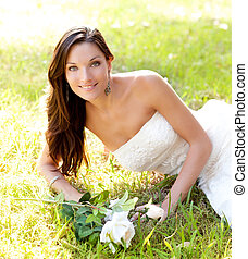 bride woman lying in park grass