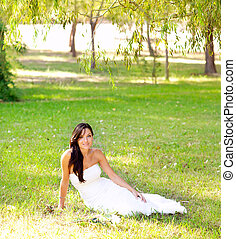 bride woman sitting in park green grass