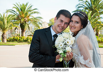 bridegroom and bride on background of the green palms