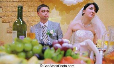 bridegroom and bride sits at wedding table and rocks