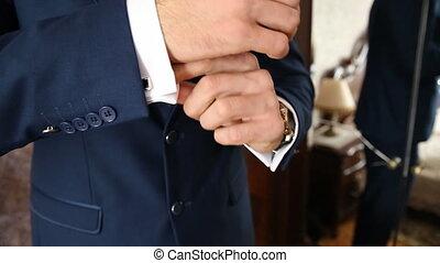 Bridegroom corrects the cuffs. Cufflinks are dressed -...