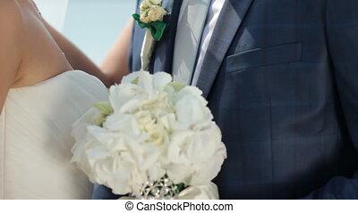bridegroom embraces the tender bride's waist