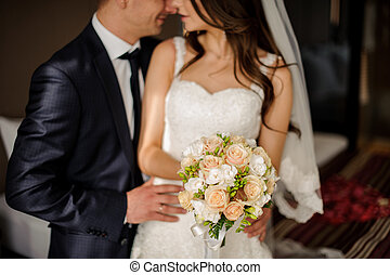 bridegroom is going to kiss charming bride with a bouquet -...