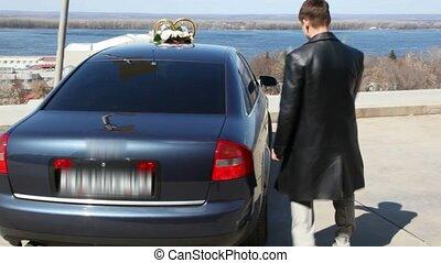 bridegroom opens door of car and offers hand to bride -...
