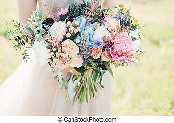 bride's hands hold beautiful bridal bouquet of peony. fine...