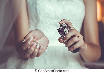 Bride's hands holding a bottle with parfumes