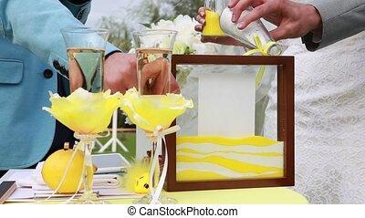 Brides hands sprinkled colored sand for sand wedding...