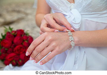 Bride's hands with the bracelet. Wedding bouquet in the background.