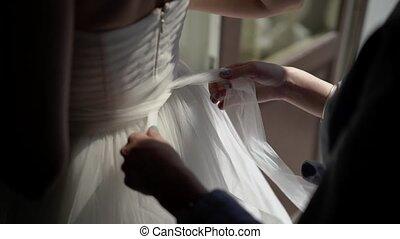 Bridesmaid helping bride put on belt closeup