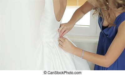 Bridesmaid helping bride with dress