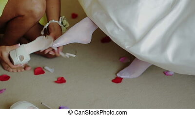 Bridesmaid Helping to Bride Put on Her Shoes
