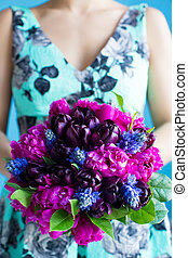 bridesmaid holds a wedding bouquet of tulips and pions in...