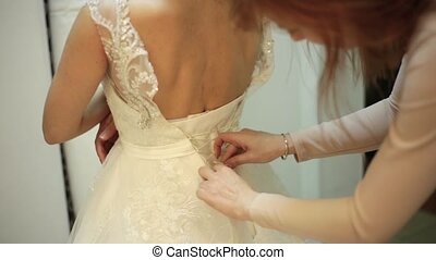 Bridesmaid is lacing wedding dress for beautiful yaung woman...