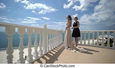 Bridesmaid lace dress bride on the terrace. Wedding at sea.