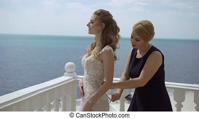 Bridesmaid lace dress bride on the terrace. Wedding at sea....