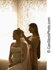 Bridesmaid placing veil. - Indian bridesmaid placing veil on...
