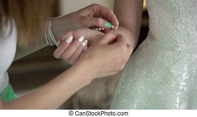 Bridesmaid put on bracelet to bride