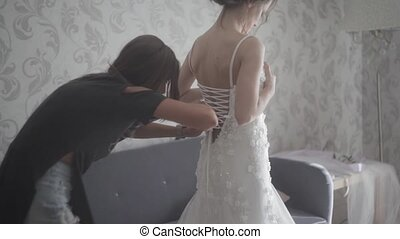 Bridesmaid tying bow on wedding dress. Bride getting ready...