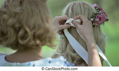 Bridesmaid tying headband for beautiful blond bride on her...