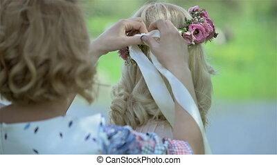 Bridesmaid tying headband for beautiful blond bride on her...