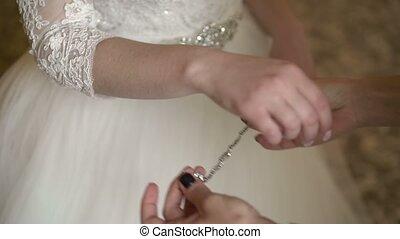 Bridesmaid wearing bracelet to bride hand