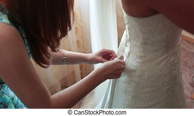 Bridesmaids buttoning on wedding dress. wedding preparations
