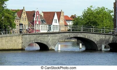 Woman rides a bicycle across a bridge in Bruges, Belgium.