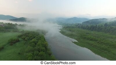 Bridge across the river is shrouded by fog. Aerial view