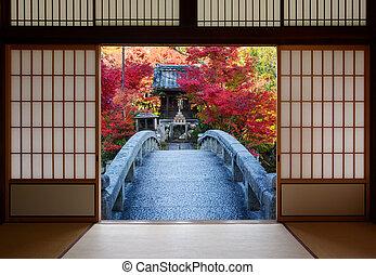 Bridge and autumn trees seen through open doors of a ...