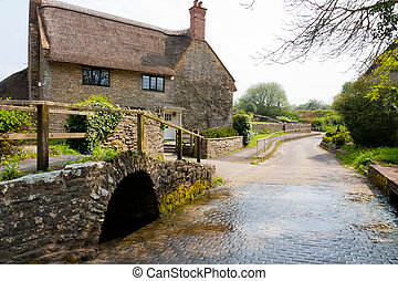 Bridge and river ford in the Dorset village of Melbury Osmond with a cottage in the background.