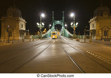 Bridge by night with tram in the di