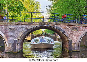 Bridge canal cruise - Canal cruise boat goes under the...