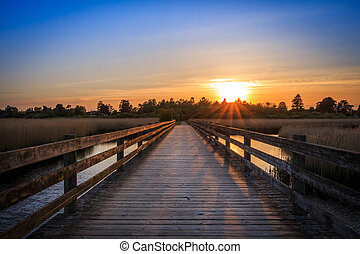 Bridge crossing sea at sunset