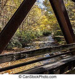 Bridge Frames Fall Colors Along Creek