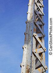 Vertical painted and rusted steel bridge beam against blue sky