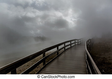 bridge in fog - wooden bridge engulfed by dense fog