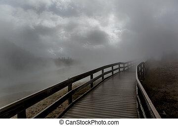 wooden bridge engulfed by dense fog