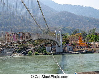 Bridge Laxman Jhula with Pedestrians, on the Holy Ganges river flows through Rishikesh (world capital of Yoga) - holy city for the Hindus
