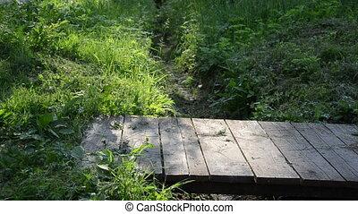bridge man boots - over a wooden bridge of planks across the...