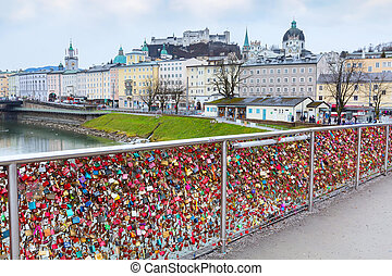 Bridge of locks and Salzburg castle across Salzach river in Austria