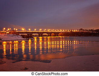 Bridge on the River Dnieper in the evening. Lantern light is reflected in the frozen ice, city