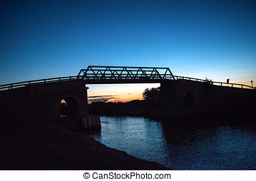 Bridge over canal at sunset