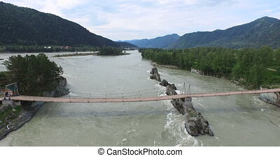 Bridge over Katun river in flood. Altay, Russia