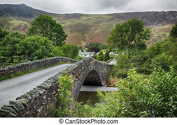 Bridge over small river at Grange in Lake District -...