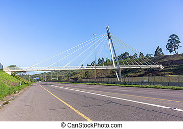Bridge pedestrian walkway   new industrial engineering design over road highway  detail steel support cables attached to vertical beam against blue sky
