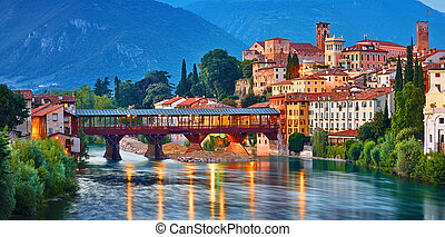 Bridge Ponte degli Alpini at river Brenta Bassano del grappa Italy. Panoramic view at old town with vintage building and tower and wooden bridge at background Alpine mountains scenic landscape evening sunset.