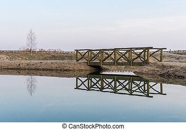 Bridge reflection in water. Early spring evening