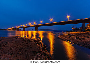 Bridge - Steel bridge across river at night with artificial...
