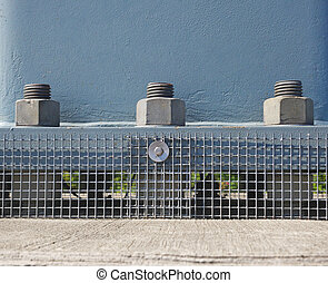 abstract view of a portion of the bridge support showing 3 bolts nd nuts